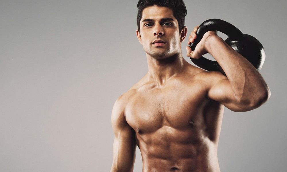 Handsome muscular man holding kettle bell with copy space. Hispanic male athlete working out with kettlebell on grey background. Crossfit workout theme.