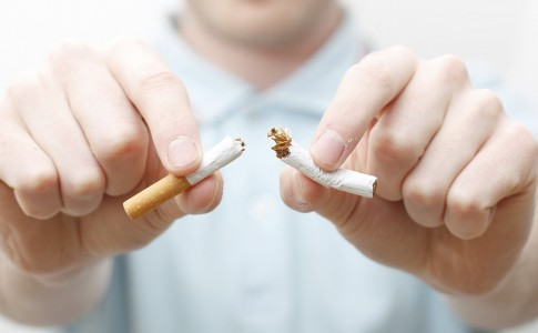 A hand crushing cigarettes