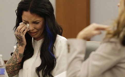 Christine Mackinday, also known as Christy Mack, cries on the witness stand as she looks at evidence photos presented by Chief Deputy District Attorney Jacqueline Bluth during a preliminary hearing for Jonathan Paul Koppenhaver, also known as War Machine, Friday, Nov. 14, 2014, in Las Vegas. Koppenhaver is accused of assaulting his former girlfriend Mackinday. (AP Photo/John Locher)