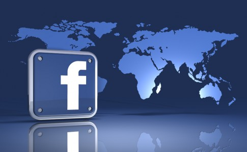 3d illustration of a facebook logo standing in front of an upright map of the world on a blue reflective surface